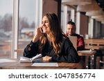 happy businesswoman sitting at... | Shutterstock . vector #1047856774