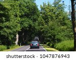 cars driving in a row on a tree ... | Shutterstock . vector #1047876943