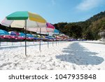 colorful sunshades on the beach | Shutterstock . vector #1047935848