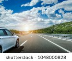 white car rushing along a high... | Shutterstock . vector #1048000828