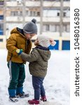Small photo of Little brother and sister love kissing on snow in winter