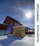 Small photo of New wooden sauna (banya, russian bathhouse) standing among white snow. Cottage at the back. Summer winter day somethere in Siberia. With empty space for text.