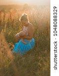 breastfeeding mother in outdoor ... | Shutterstock . vector #1048088329