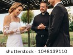 woman read vows from paper for... | Shutterstock . vector #1048139110