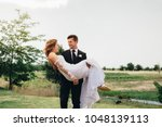 young groom carrying his... | Shutterstock . vector #1048139113