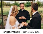 male priest marries a couple in ... | Shutterstock . vector #1048139128