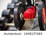 woman's hand holds dumbbell | Shutterstock . vector #1048157683