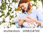 loving mother with her newborn... | Shutterstock . vector #1048218760