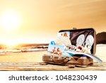 summer suitcase on wooden desk... | Shutterstock . vector #1048230439