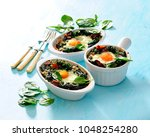 baked eggs with spinach and... | Shutterstock . vector #1048254280