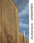 Small photo of Outdoor view of a large wooden facade made of long brown vertical planks. Inox aeration tube fixed on the wall. Grey blue sky in background. Bright colors and rough surface. Modern architecture view.