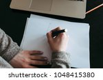 Small photo of women's hands lie on a sheet of paper and draw something with a pen, next to it lies laptop...
