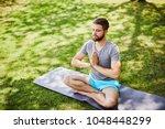 Young Man Meditating Outdoors...