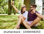young couple taking selfie... | Shutterstock . vector #1048448353
