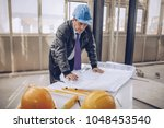 an older architect in a blue... | Shutterstock . vector #1048453540