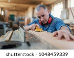 man doing woodwork in carpentry.... | Shutterstock . vector #1048459339