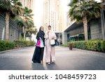 arabic women shopping outdoors... | Shutterstock . vector #1048459723