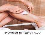 Close-up on young woman doing depilation on legs - stock photo