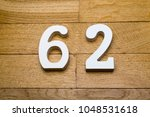 Small photo of Numbers sixty-two on the wooden parquet floor in the background.