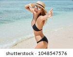 shot of joyful female in shades ... | Shutterstock . vector #1048547576