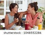 two happy overjoyed women sit... | Shutterstock . vector #1048552286