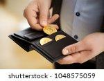 businessman holding bitcoin... | Shutterstock . vector #1048575059