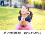little girl praying in the... | Shutterstock . vector #1048592918