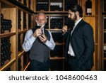 winemakers in wine cellar... | Shutterstock . vector #1048600463