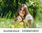 Beautiful young woman laying on grass with dandelion flowers in park