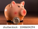 piggy bank with bitcoin on top... | Shutterstock . vector #1048604294
