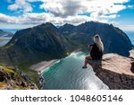 adventurous woman looking down... | Shutterstock . vector #1048605146