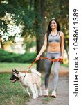 sports woman walking with dog... | Shutterstock . vector #1048611389