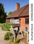 Small photo of CHAWTON, UK - JUN 8, 2013: Bakehouse and well in the garden of Chawton Cottage, an independent museum of novelist Jane Austen
