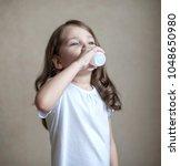 cute little girl is drinking...   Shutterstock . vector #1048650980