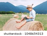 reading boy sits over the... | Shutterstock . vector #1048654313