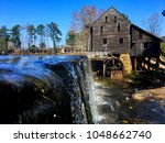 Small photo of View from just above water level of the waterfall and the old gristmill with its flume and waterwheel at Historic Yates Mill County Park at Raleigh North Carolina, Triangle area, Wake County.