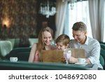 smiling family with menu in a... | Shutterstock . vector #1048692080