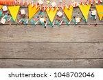border of yellow paper flags... | Shutterstock . vector #1048702046
