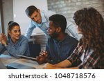 young freelance team working on ... | Shutterstock . vector #1048718576