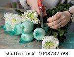 the hands of florist against... | Shutterstock . vector #1048732598