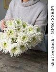 close up of flowers in hands of ... | Shutterstock . vector #1048732634