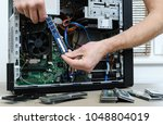 a man is holding a ram slot to... | Shutterstock . vector #1048804019
