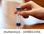 hourglass in hand as time... | Shutterstock . vector #1048811456