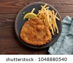 weiner schnitzel with fried... | Shutterstock . vector #1048880540