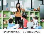 young asian woman teacher... | Shutterstock . vector #1048892933