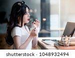 beautiful asian woman holding... | Shutterstock . vector #1048932494