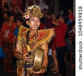 Small photo of Desa Munggu (Munggu village), Bali, Indonesia. March, 16, 2018. Member of traditional Balinese orchestra Gamelan with a gong on Ngrupuk parade conducted on the eve of Nyepi day.