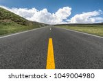 rural highway heads off to the... | Shutterstock . vector #1049004980