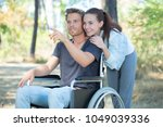 couple at wheelchair walk... | Shutterstock . vector #1049039336