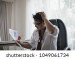 stressed asian businessman... | Shutterstock . vector #1049061734